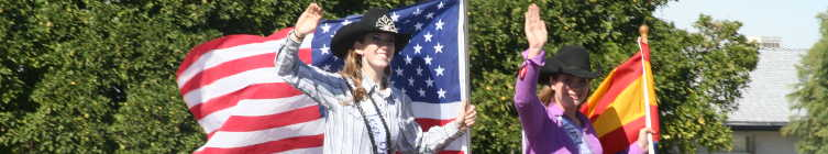 Cowgirls at Billy Moore Days parade with national and state flags