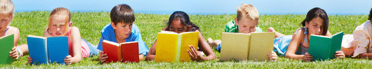 Children laying in grass reading books