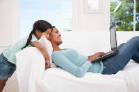 Mother and daughter lounging with laptop