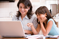 Mother and daughter smiling at laptop