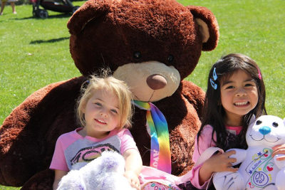 Two young girls smiling, sitting with oversized teddy bear in grass